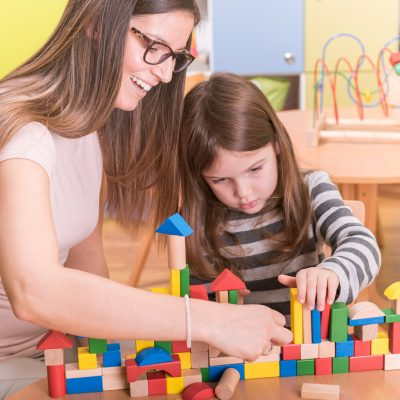 Preschool - Kindergarten Teacher and Kid Playing with Wooden Building Blocks