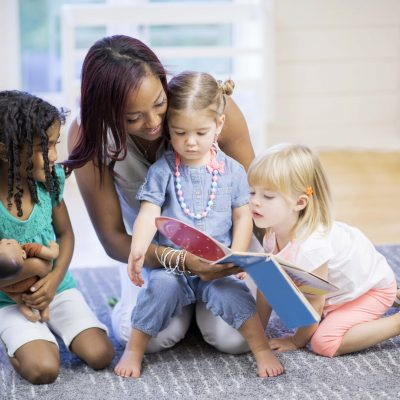 A teacher is reading a picture book the toddler students at daycare.